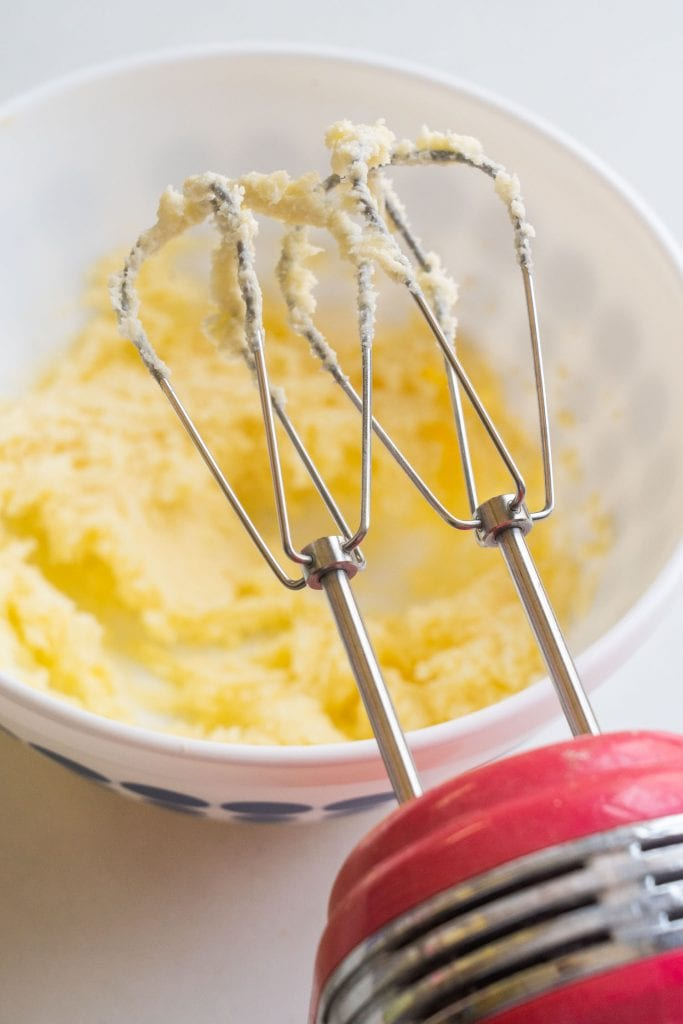 electric hand mixer with cookie batter on beaters above white bowl