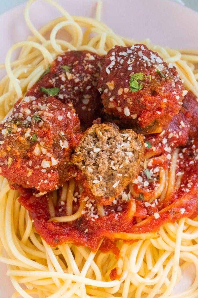 meatballs cut in half on top of spaghetti.
