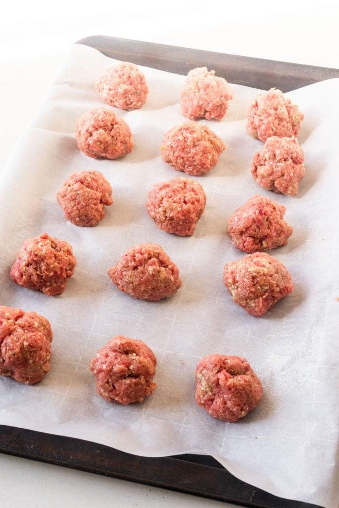 uncooked meatballs on baking sheet.