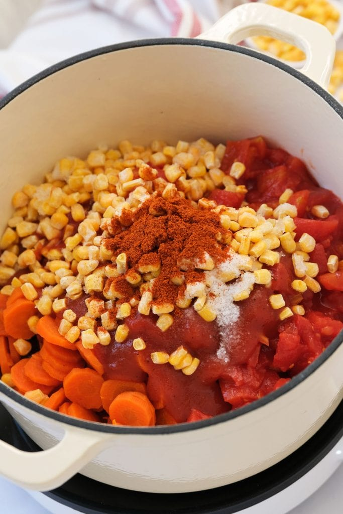 corn, tomatoes, tomato sauce, carrots, chili powder and salt being added to pot.