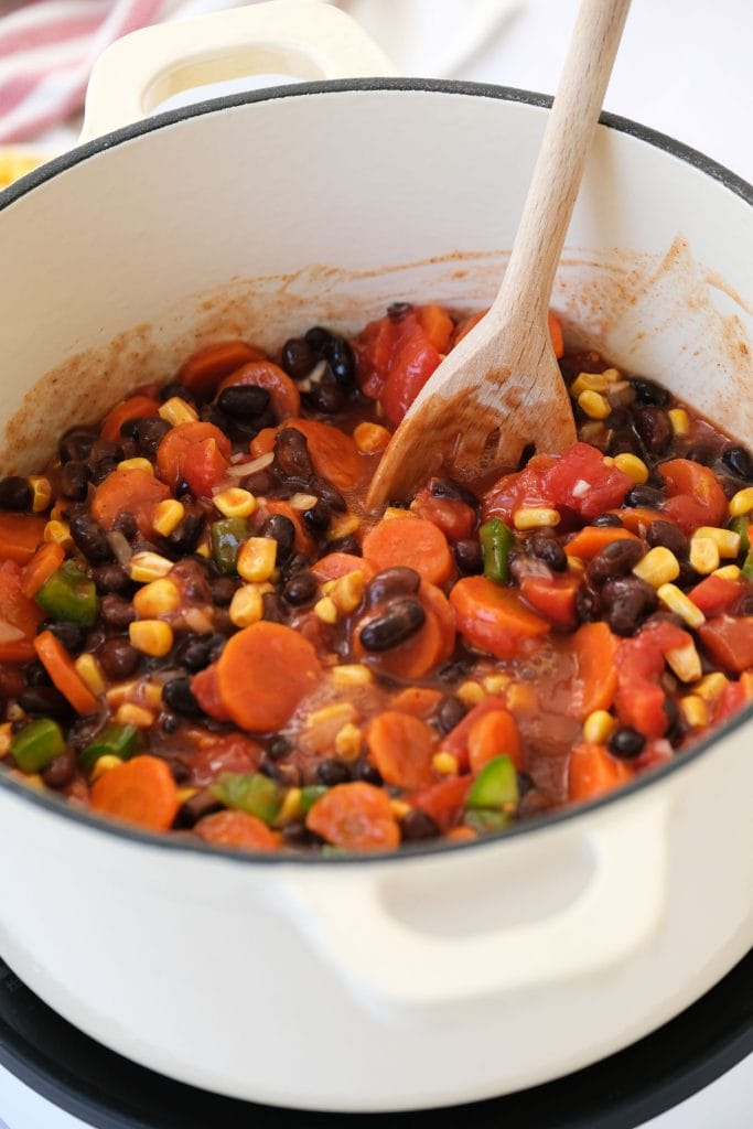 wooden spoon mixing vegetarian chili in white pot.