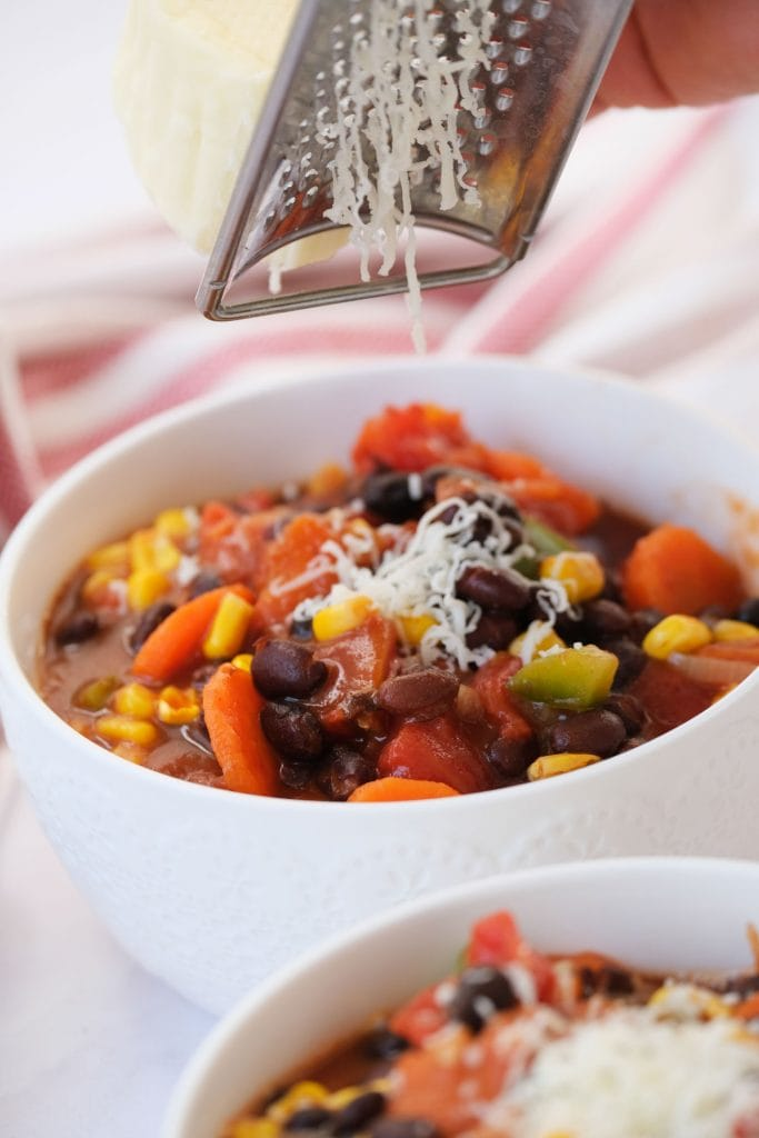 grated cheese being added on top of black bean chili in white bowl.