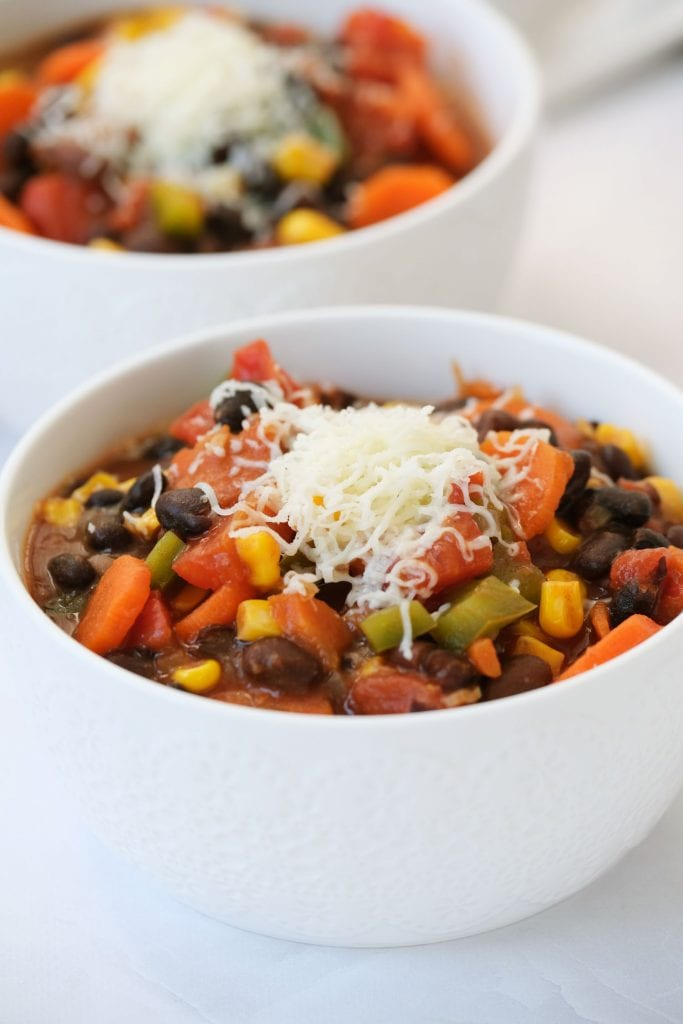 shredded cheese on top of vegetarian chili in white bowl on table, ready to be served.