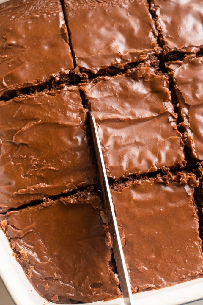 knife cutting into brownies in baking dish to makes squares.