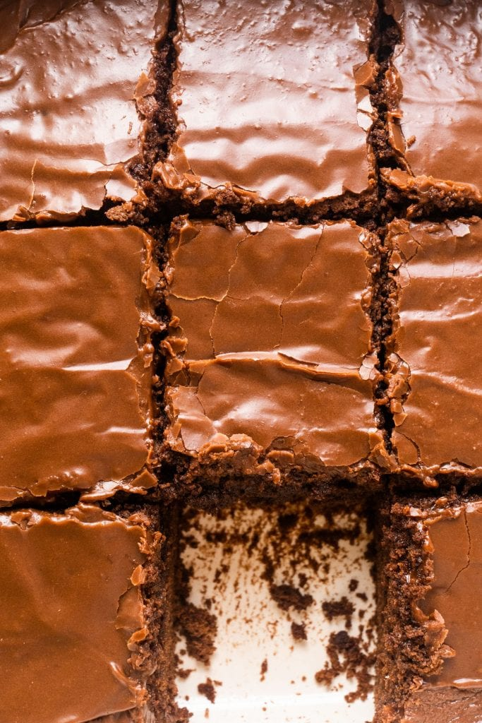 squares of chocolate brownies with buttercream frosting on top.