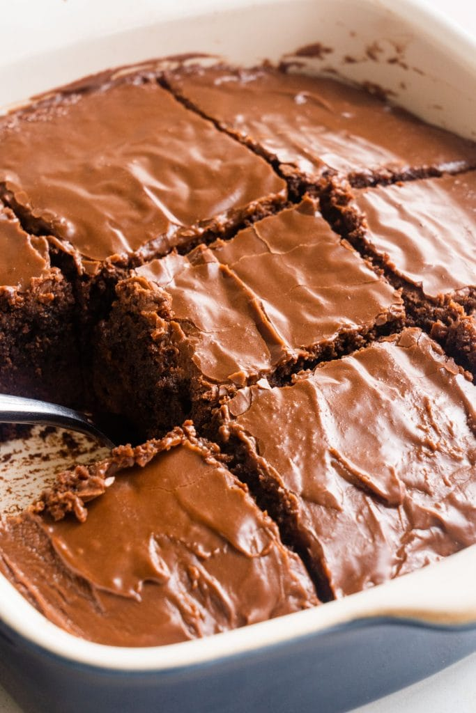 fork lifting out brownie in baking dish.