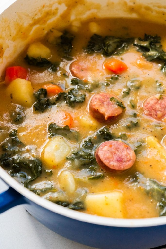 sausage and kale soup with vegetables in blue soup pot