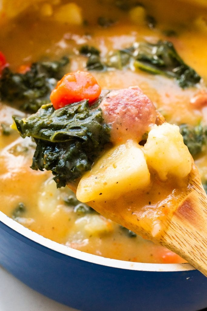 wooden spoon filled with creamy sausage, kale and potato soup.
