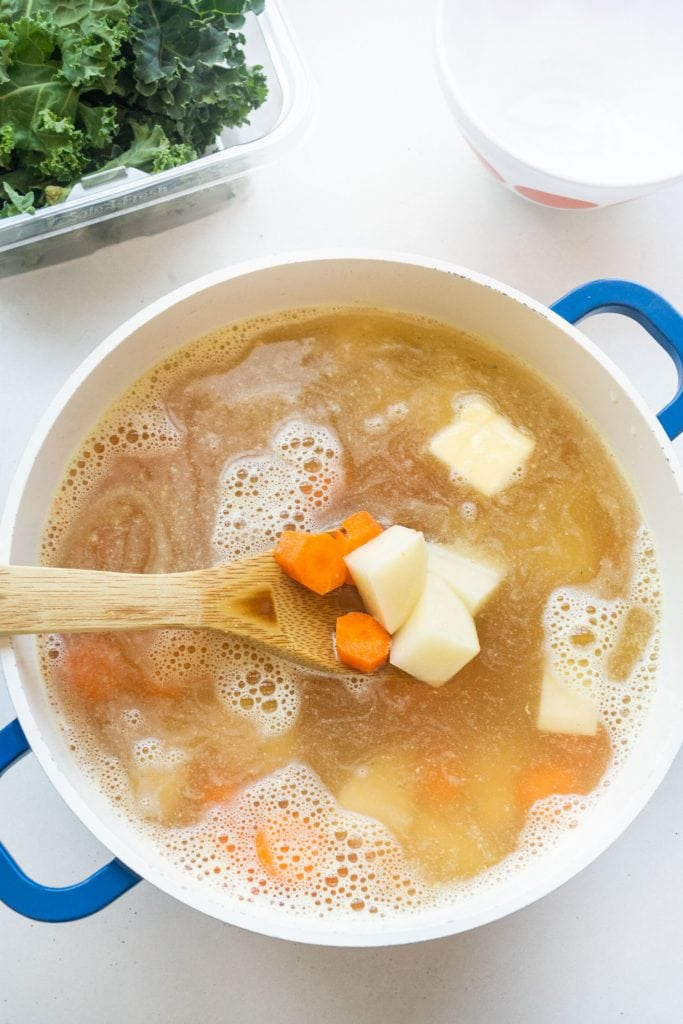 potatoes and carrots in soup pot with chicken broth and butter, ready to be cooked.