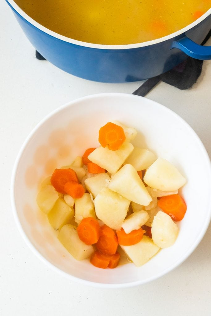 cooked potatoes and carrots in white bowl.