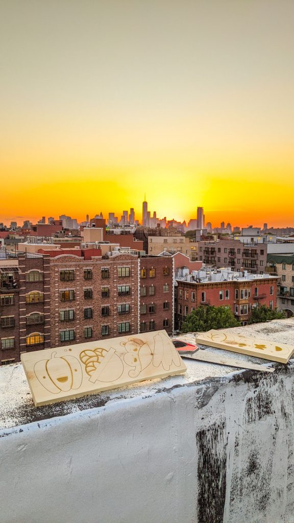 wood pieces with vegetables stenciled on them on rooftop with nyc skyline in background.
