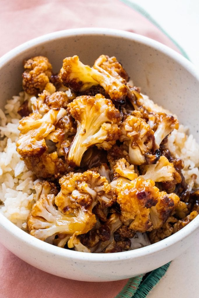 general tso's cauliflower on top of rice in bowl.