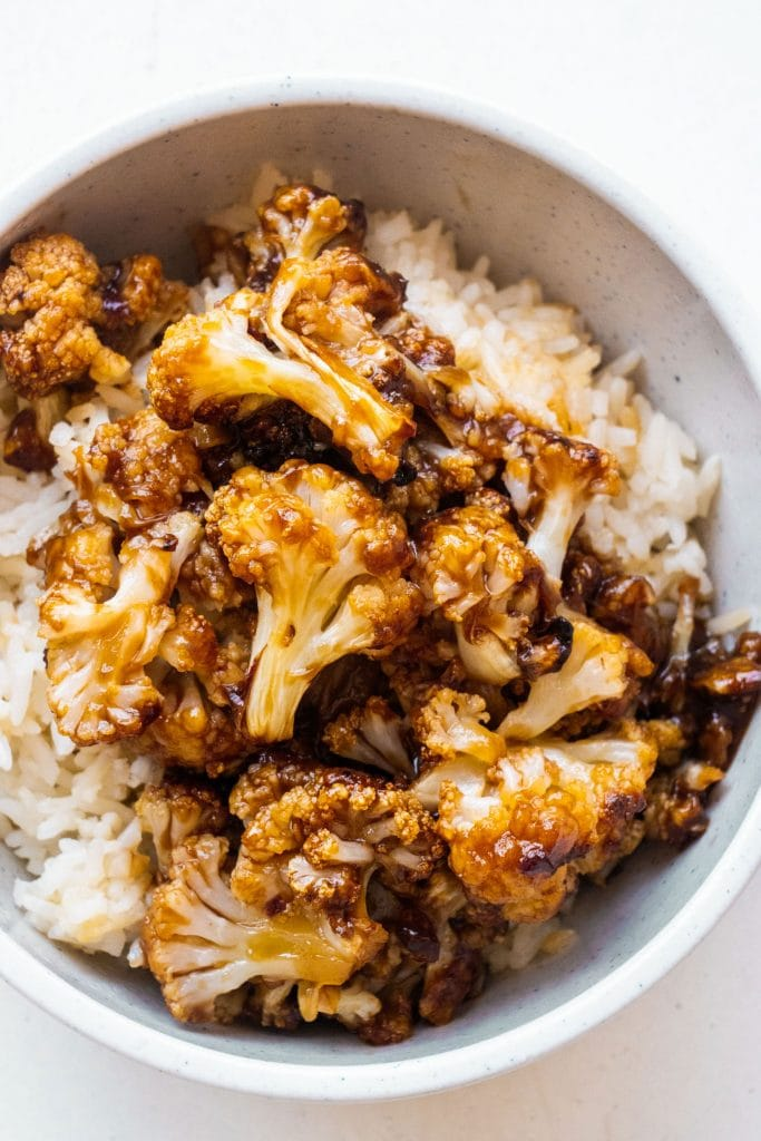 white bowl filled with rice and general tsos cauliflower.