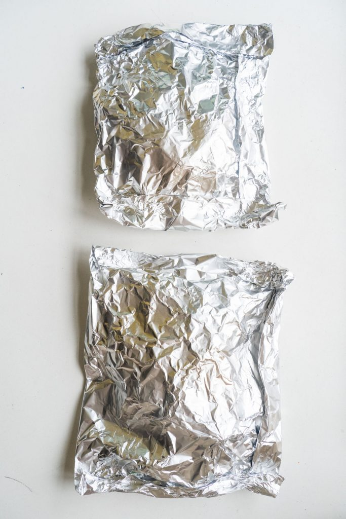 2 aluminum foil pieces on table with bok choy inside