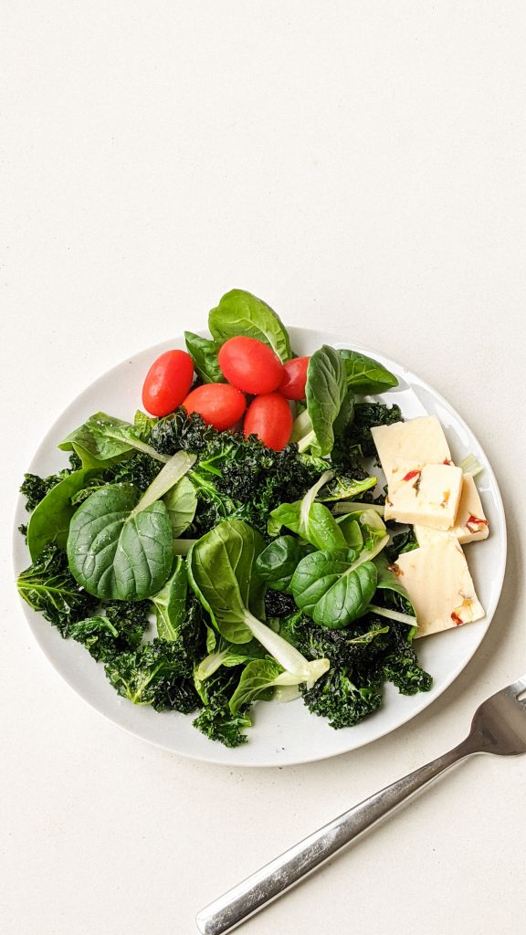 plate with fresh bok choy, kale, cheese and tomatoes on it.