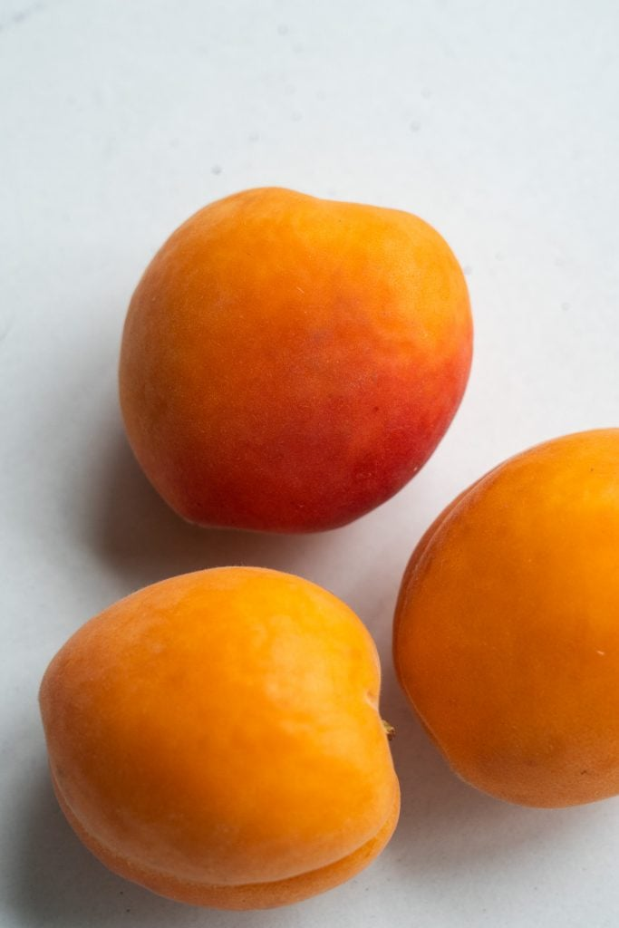3 apricots on white table.