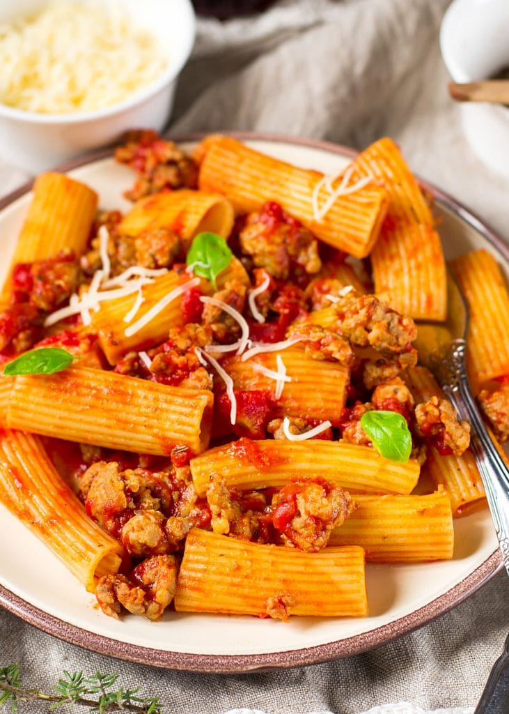 rigatoni with sausage and parmesan cheese on white plate.
