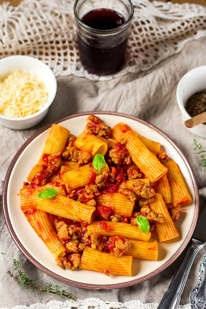 Saucy rigatoni pasta with ground sausage and basil on white plate.