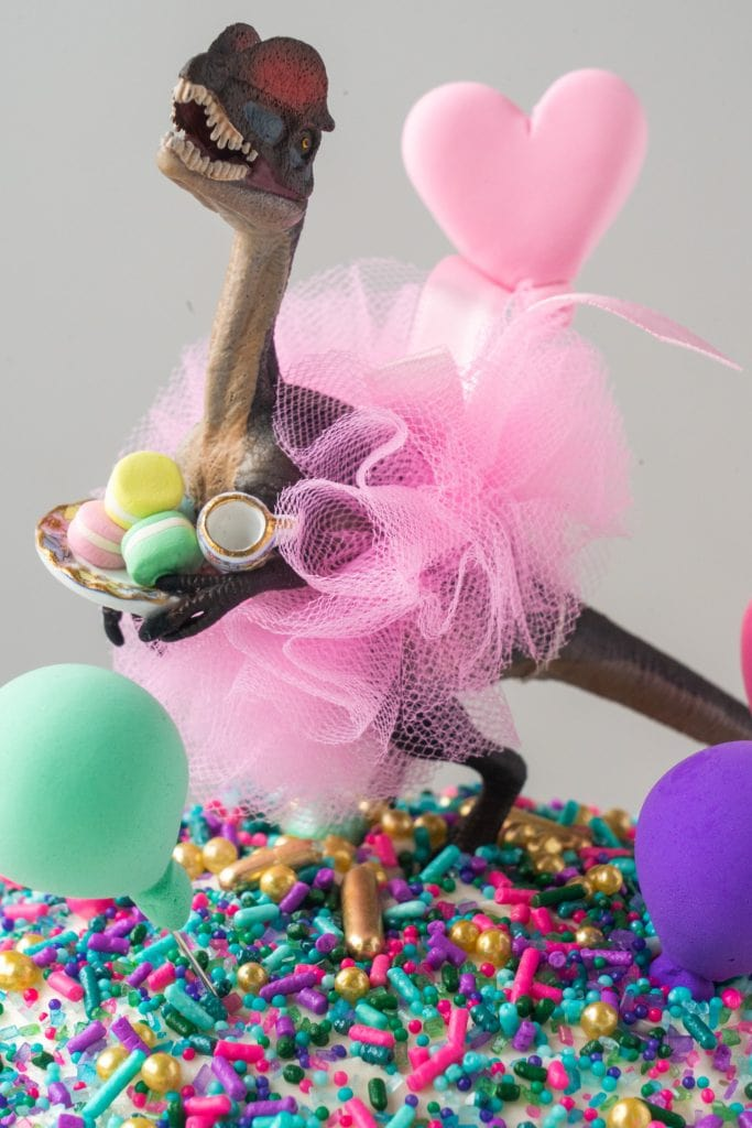 dinosaur wearing tutu on top of cake holding a plate of macarons