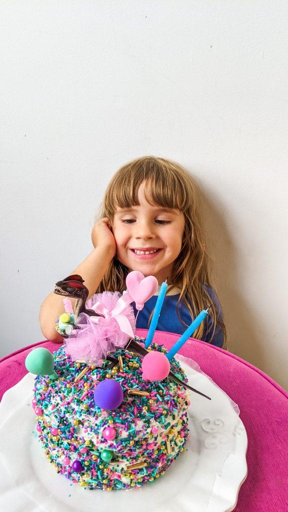 little girl sitting on floor admiring birthday cake with dinosaur on it.