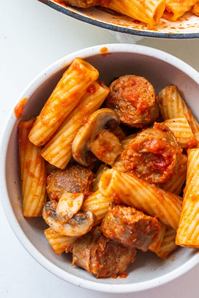 bowl filled with sausage, pasta and mushrooms.