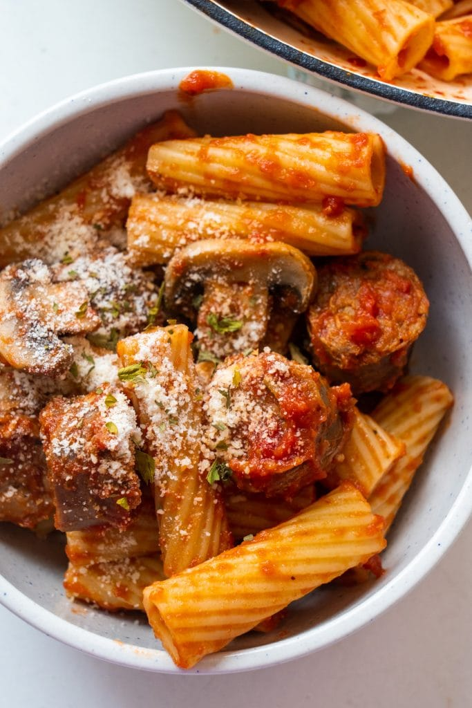 bowl filled with rigatoni pasta with parmesan cheese on top.