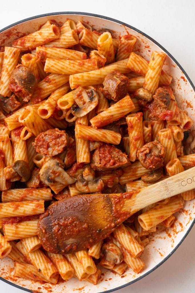 pasta with sausage in skillet with wooden spoon stirring.