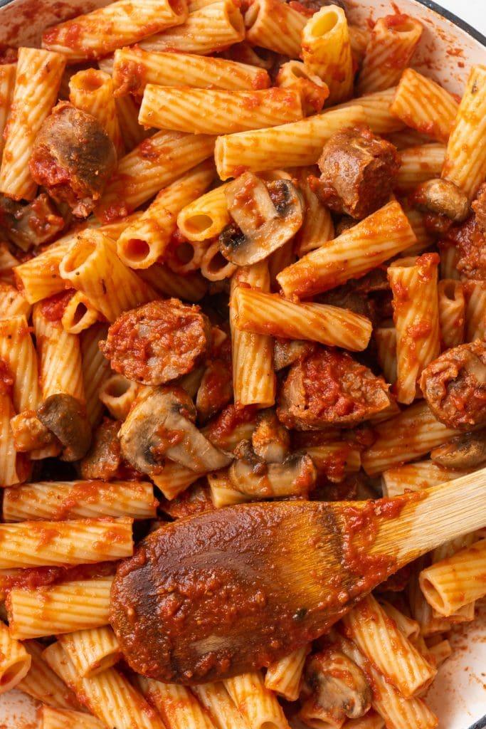 saucy rigatoni pasta with mushrooms and italian sausage in pan.