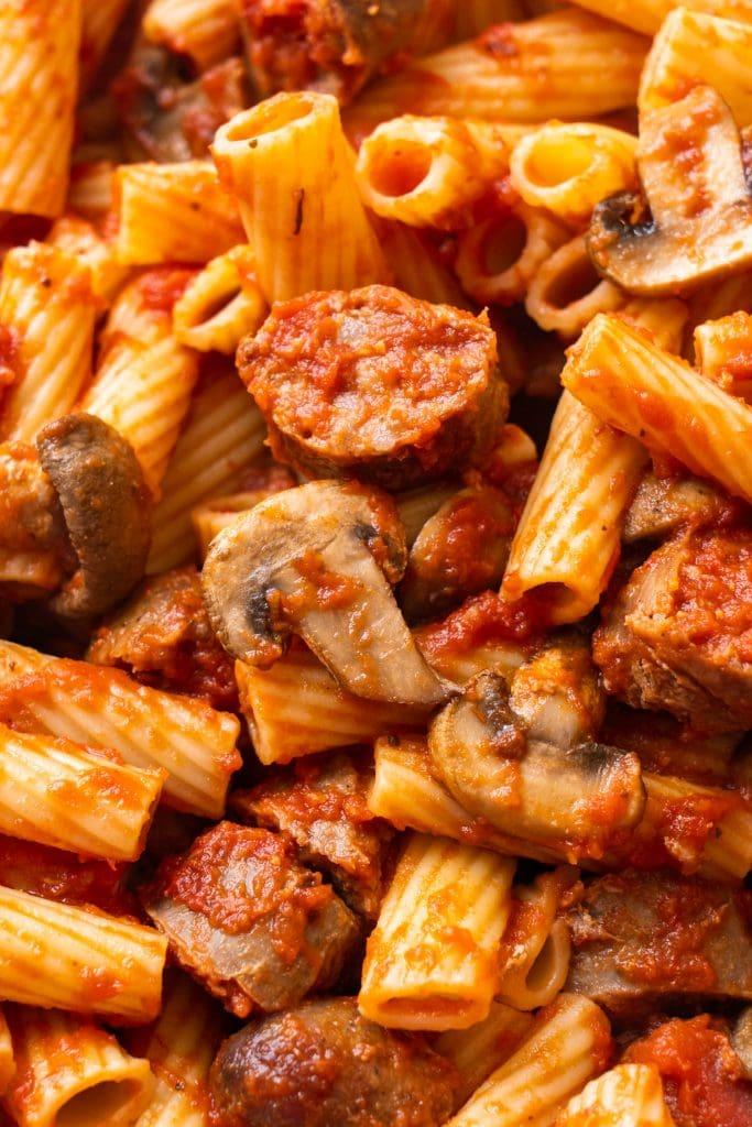 closeup of saucy rigatoni with mushrooms and sausage.