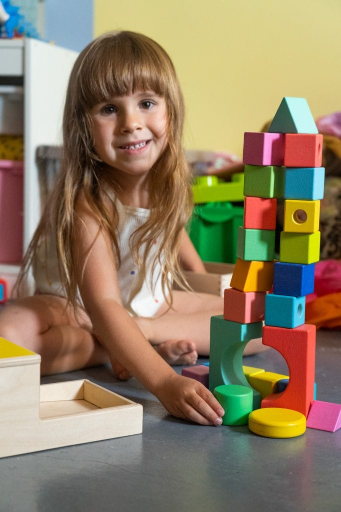 4 year old girl playing with lovevery wooden block set.