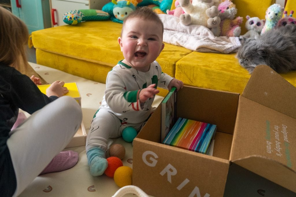 baby smiling, opening lovevery inspector play kit.