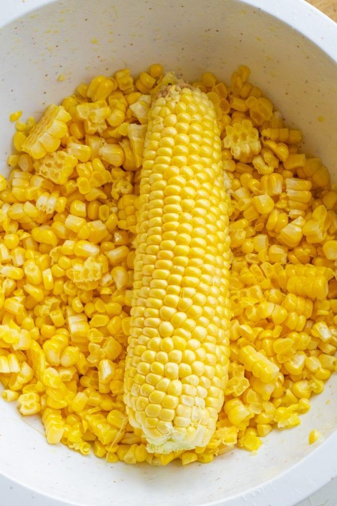 fresh corn cob in a bowl of kernels.