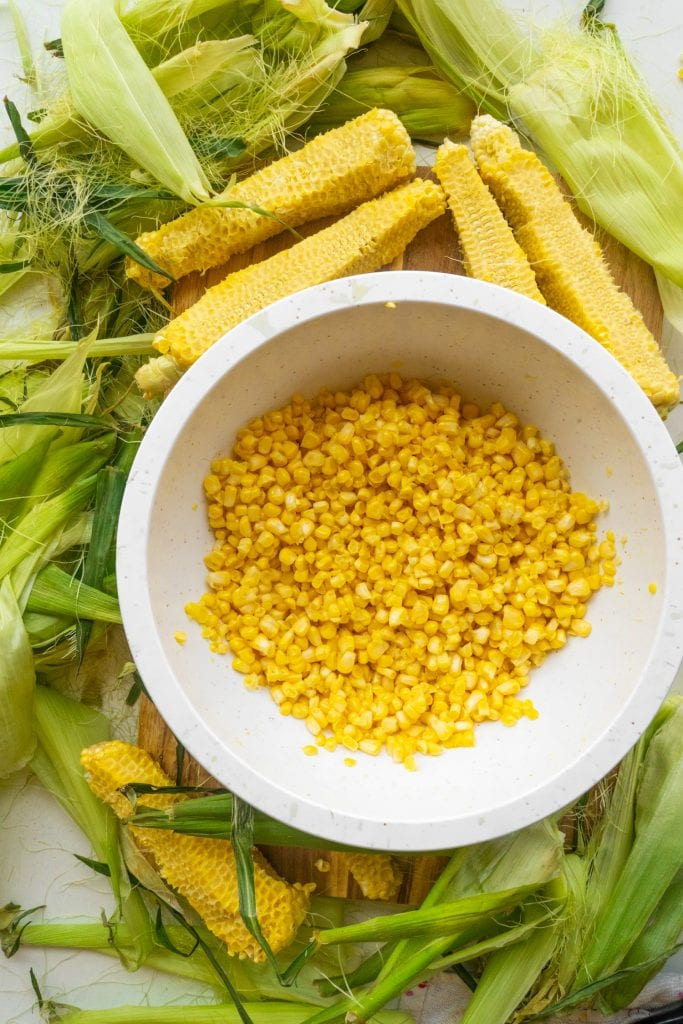 a bowl of corn kernels surrounded by corn cobs and tassels.