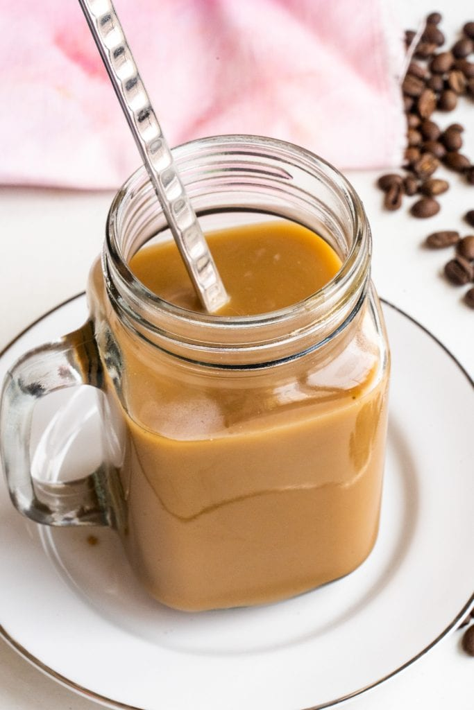 spoon in glass mason jar filled with coffee on white table.