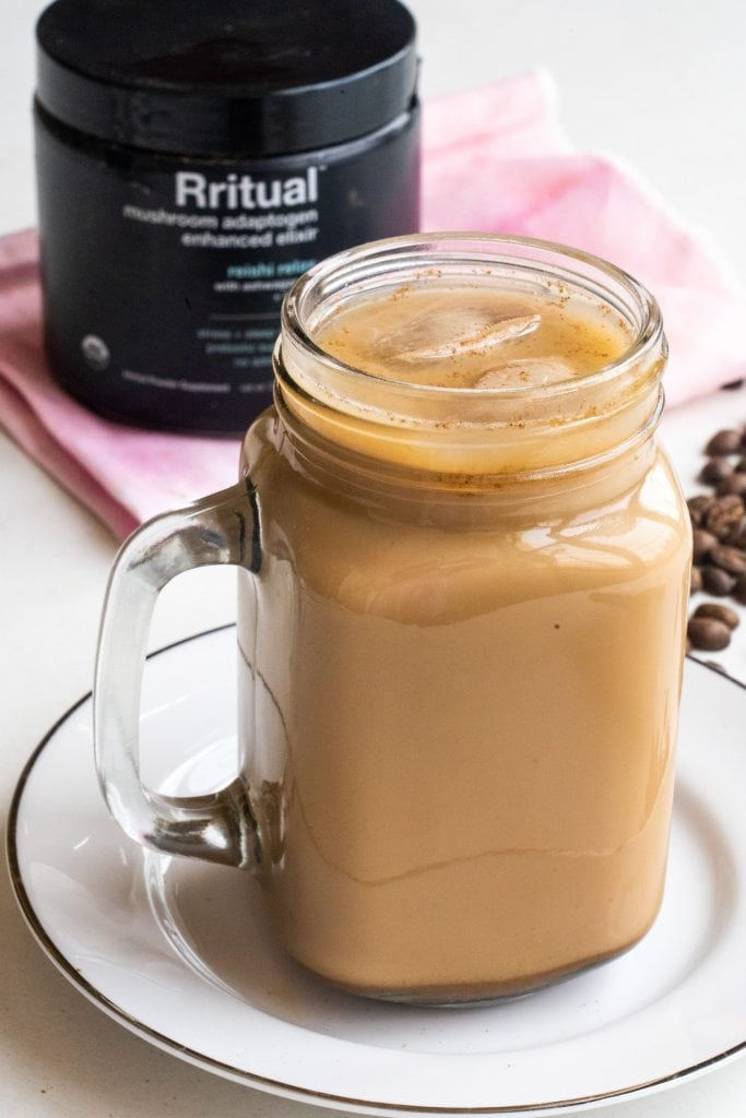glass jar filled with iced coffee on white serving plate.