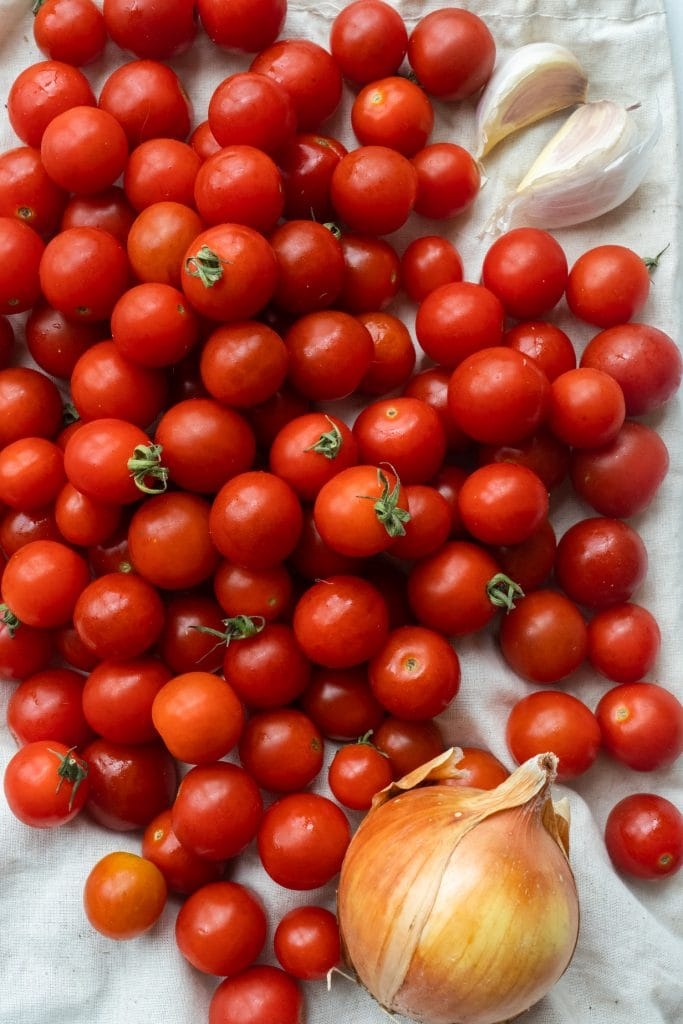 cherry tomatoes, onion and garlic on table.