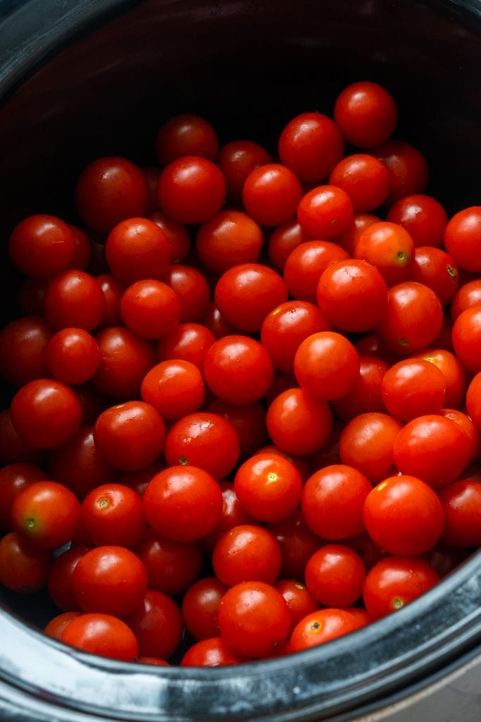 8 cups of cherry tomatoes in slow cooker bowl.