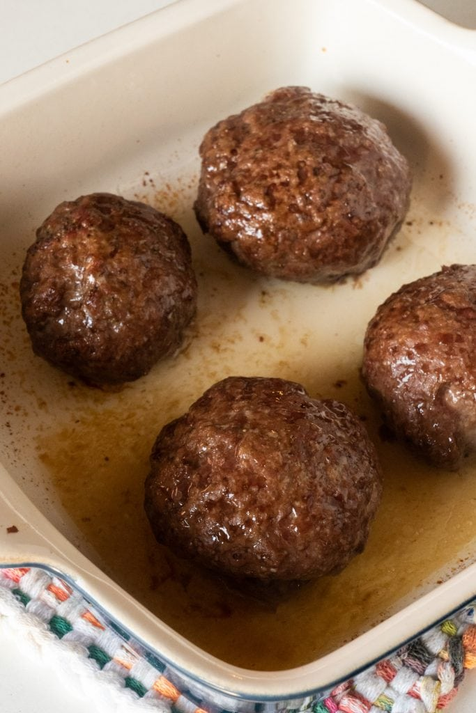 baked ground beef burgers in baking dish.