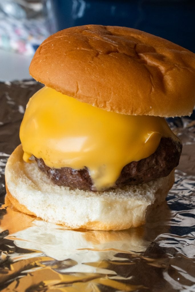 ground beef burger with melted cheese on hamburger bun.