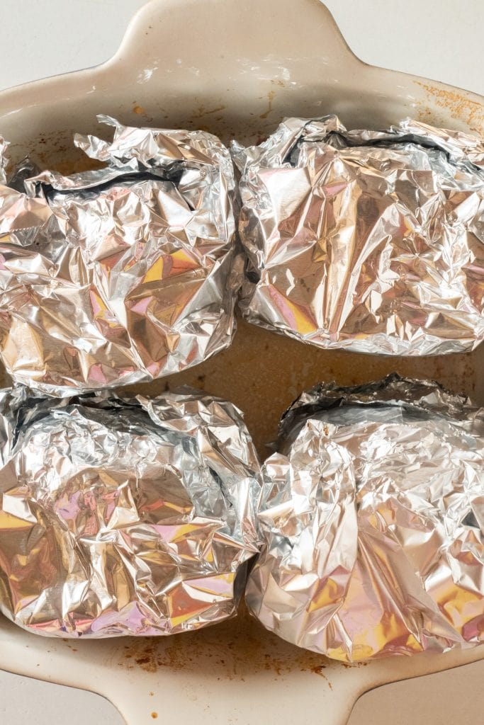 burgers wrapped in aluminum foil in baking dish.