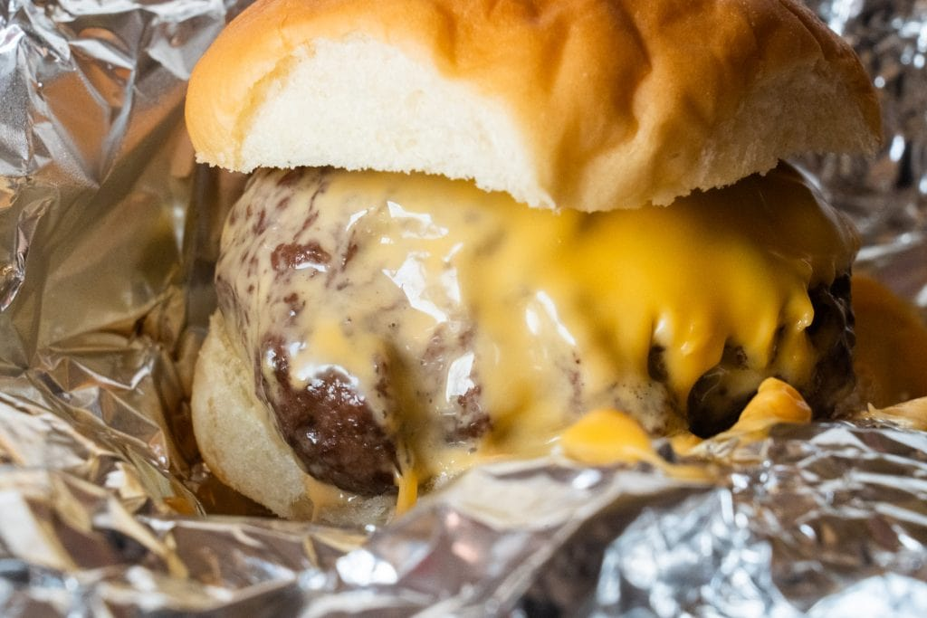 ooey gooey cheesey burger with bun in foil.