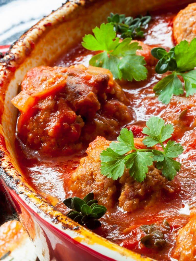 closeup of meatballs in tomato sauce with fresh oregano in baking dish.