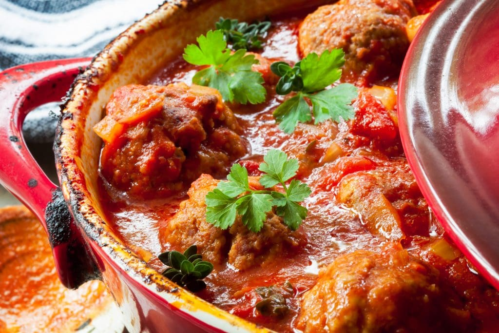 red baking dish with savory saucy meatballs inside of it.