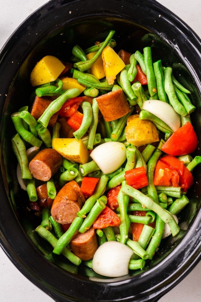 raw vegetables and kielbasa in slow cooker before it gets cooked.