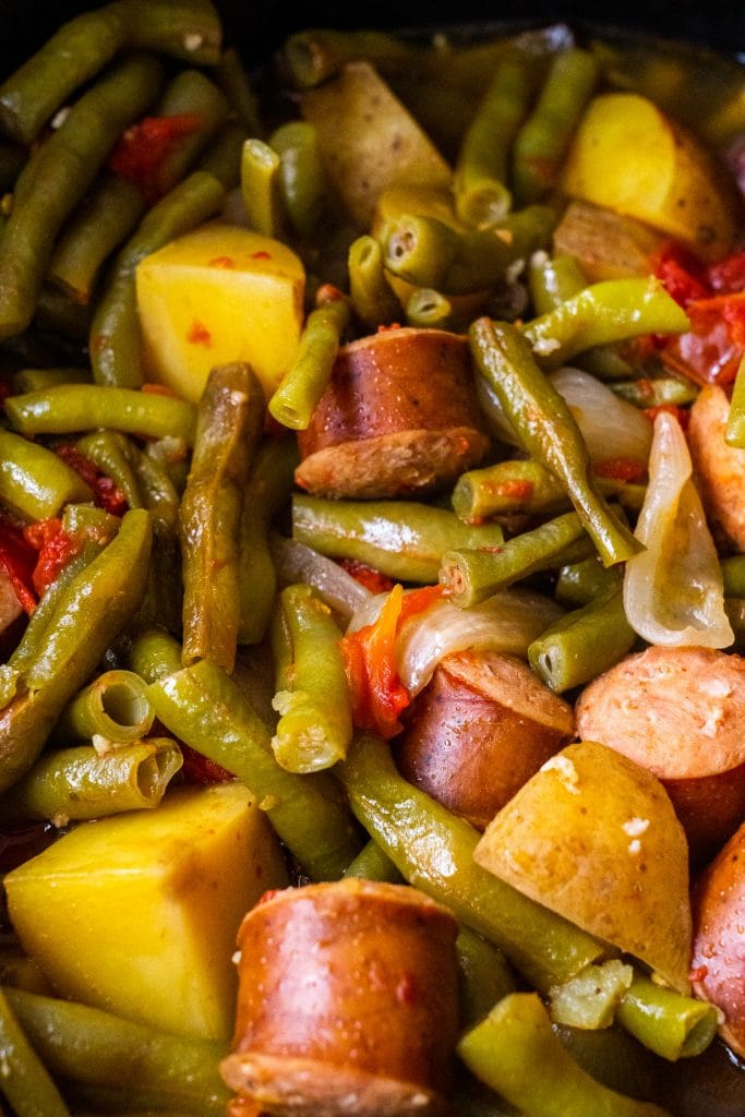 cooked green beans and kielbasa sausage, potatoes and onions in crockpot.