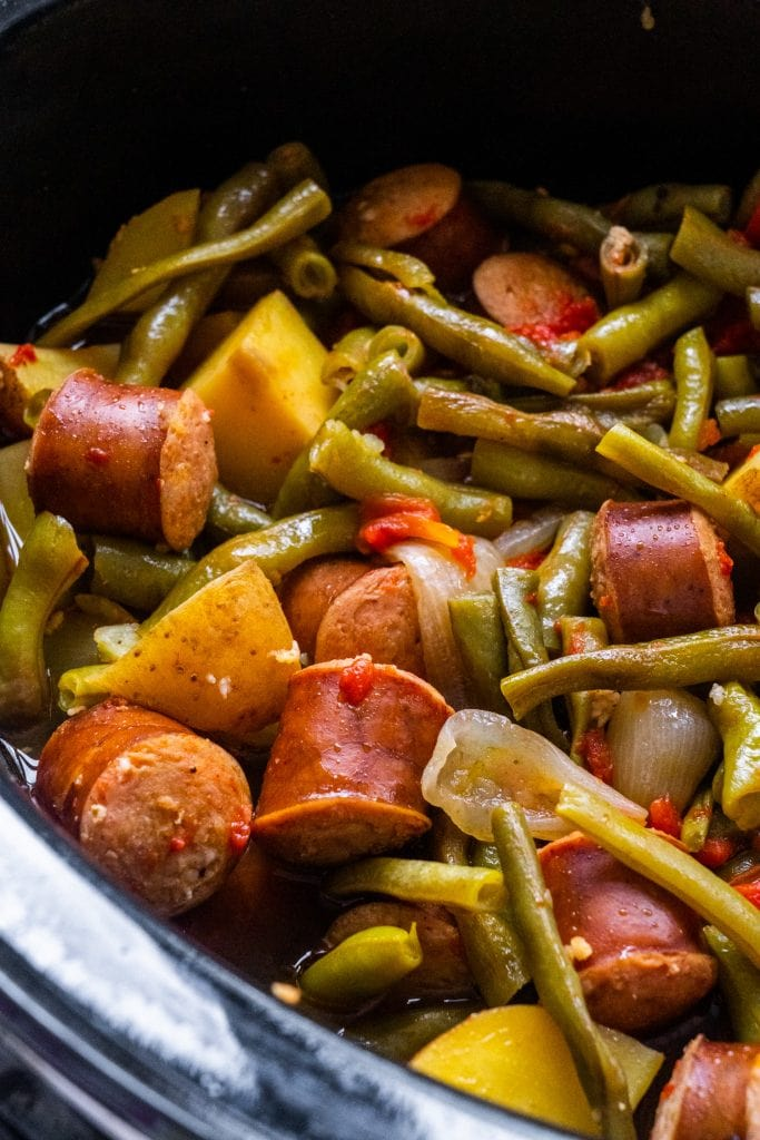 vegetables and sausage cooked in slow cooker bowl.