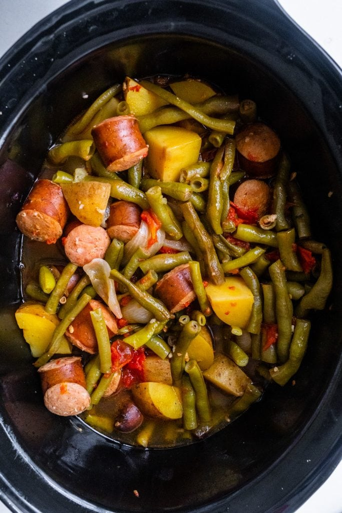 slow cooker pot filled with kielbasa sausage, green beans, potatoes, onions and tomatoes in broth.