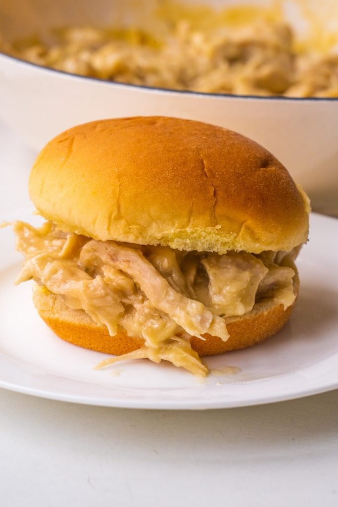 chicken and gravy sandwich on white plate.