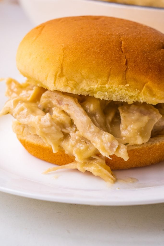 chicken and gravy on hamburger bun on white plate.