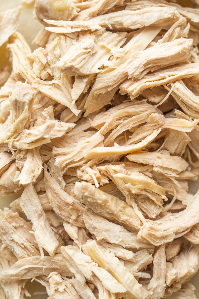 cooked shredded chicken breast on cutting board.